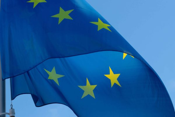 Flag of the European Union, which is blue with a circle of yellow stars.
