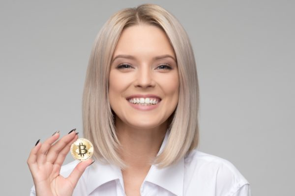 Millennial blond woman in a white shirt holding a bitcoin and smiling.
