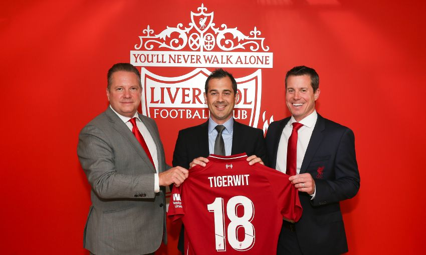 New trading partners TigerWit and Liverpool FC pose with a soccer kit that says TigerWit.